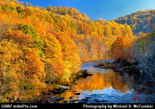 Scenic Overlook's View of a Setting Sun Cast Against Fall Foliage Picture